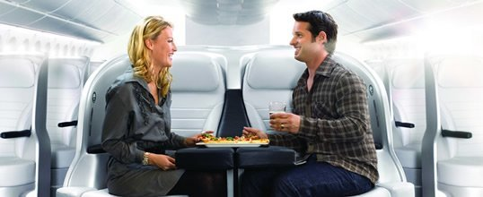 Premium Economy couple dining together.